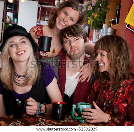 Four friends enjoying time together at a cafe - stock photo