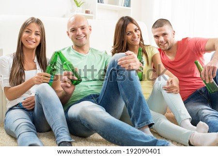 Four friends enjoying with beer together at the home party.