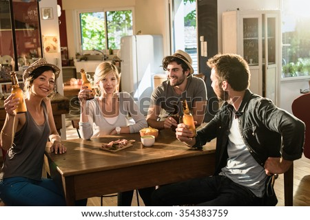 Four friends having a drink after work. They are sitting at a wooden table lifting their bottles of beer in a cozy house. They are smiling and looking at camera, wearing casual clothes and hats.