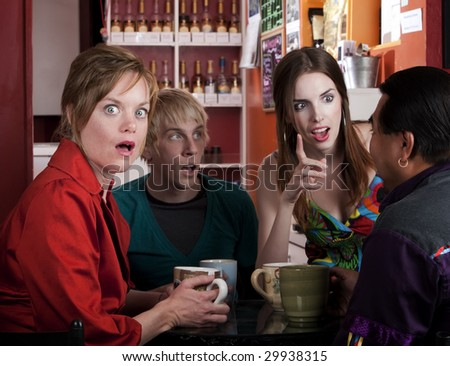 Four friends having an animated discussion in a coffee house - stock photo