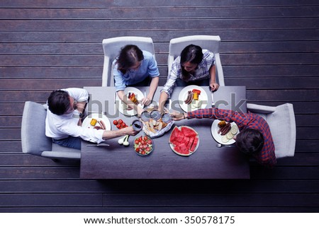 Four friends having dinner, top view - stock photo