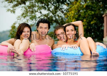 Four friends having fun in the pool - stock photo