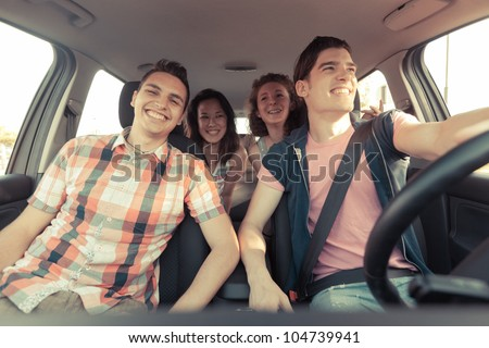 Four Friends in a Car Leaving For Vacation - stock photo