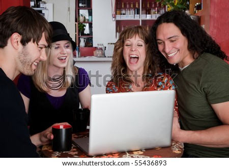 Four friends in a coffee house with laptop computer - stock photo