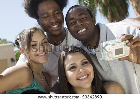 Four friends in back yard photographing selves - stock photo
