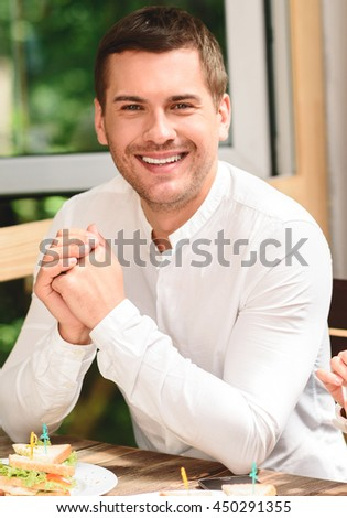 Four friends in coffee shop using laptop - stock photo