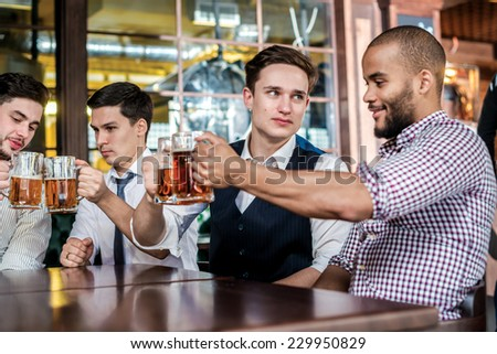 Four friends in the bar clink beer. Four friends sitting at a table drinking glasses of beer in their hands. Friends having fun together - stock photo