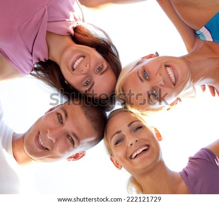 Four friends in the park making silly pictures and having fun. Low angle shot. - stock photo