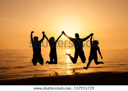 Four friends jumping on the beach at sunset  - stock photo