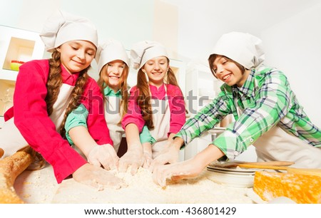 Four friends kneading bakery dough at the kitchen - stock photo