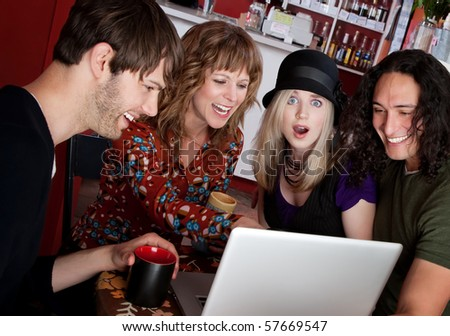 Four friends laughing at a video on a laptop - stock photo