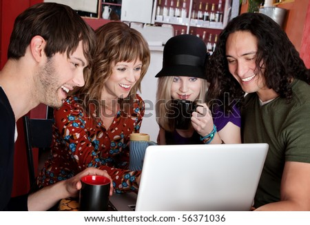 Four friends laughing at content on a laptop - stock photo