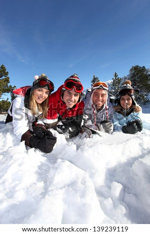 Four friends laying in the snow - stock photo