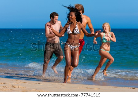 Four friends - men and women - on the beach having lots of fun in their vacation running through the water