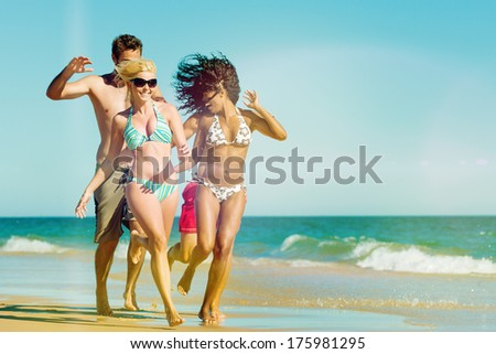 Four friends - men and women - on the ocean beach having lots of fun in their vacation running through the water - stock photo