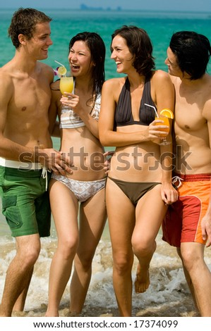 Four friends on the beach with drinks - stock photo