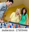 Four friends playing table football at home - stock photo