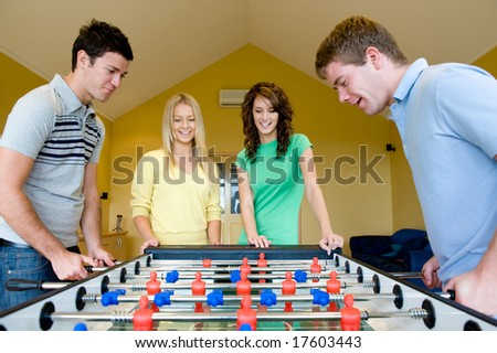 Four friends playing table football at home