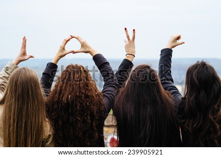 Four friends show love hands - stock photo