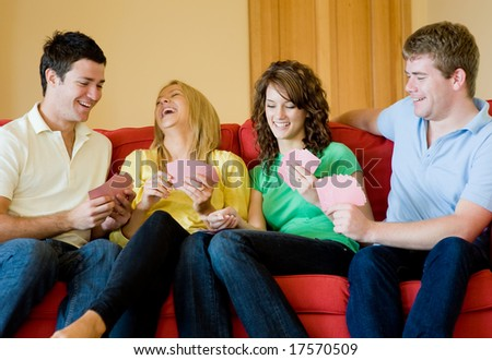 Four friends sitting at home on the sofa playing cards