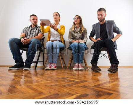 Four friends sitting in a waiting room and talking