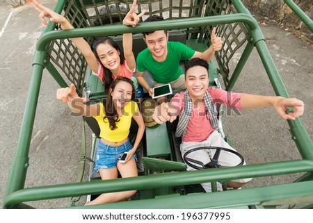 Four friends sitting in the car with their hands up, view from the top - stock photo