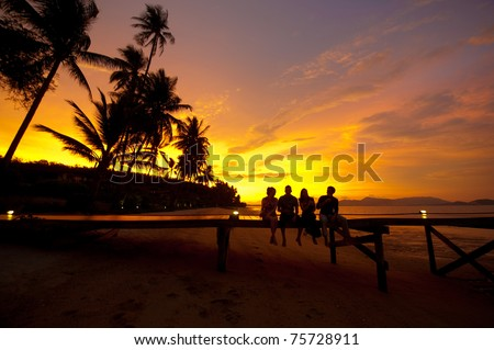 Four friends sitting on a jetty on a tropical island enjoying drinks at sunset