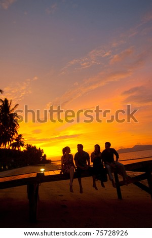 Four friends sitting on a jetty on a tropical island enjoying drinks at sunset - stock photo