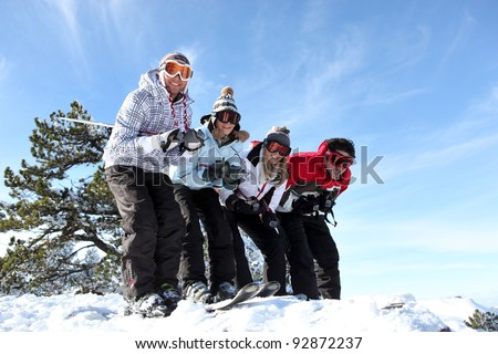 Four friends skiing together on holiday - stock photo