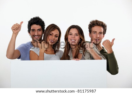 Four friends stood with blank message board - stock photo