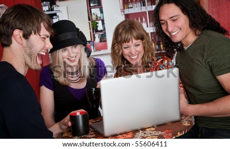 Four friends viewing something on a laptop in a cafe - stock photo