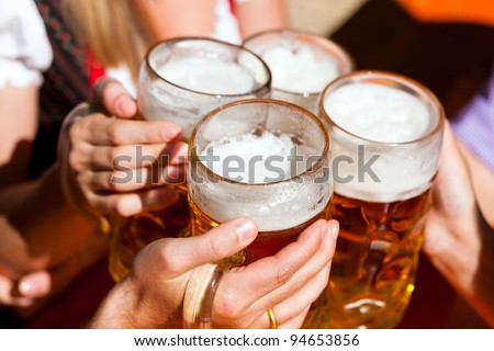Four friends with a fresh beer in a Beer garden; close-up on beer stein - stock photo