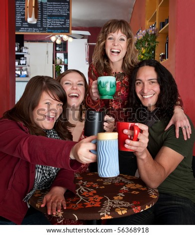 Four friends with mugs toasting at a cafe - stock photo