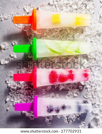 Four frozen fresh fruit popsicles with different natural flavors on bright colored plastic sticks, aligned on crushed ice, high-angle close-up - stock photo