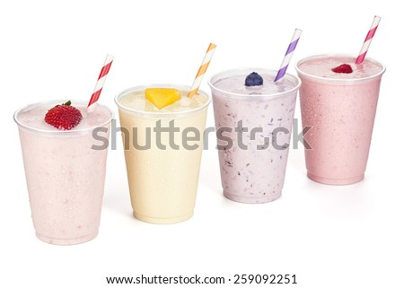 Four Fruity Yogurt Smoothies Isolated on White Background with Fruit Garnishes and Striped Straws