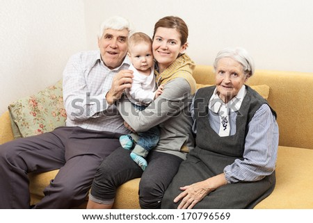 Four generation family sitting on sofa at home - stock photo