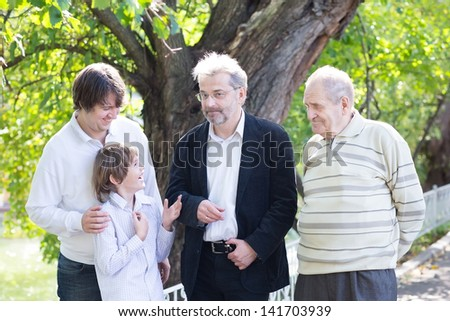 Four generation of men laughing and talking in the garden - stock photo