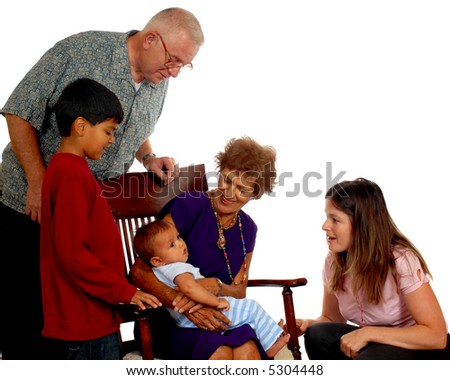 Four generations -- great grandmother holding the youngest (who is sick with a rash), while the baby's mother, brother and grandpa look on. - stock photo