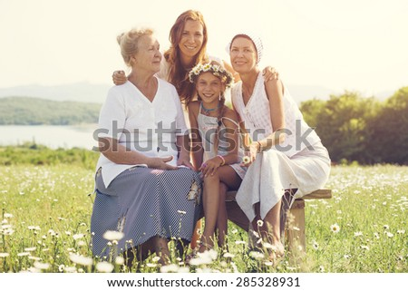 Four generations of beautiful women sitting together in a camomile field and smiling - stock photo