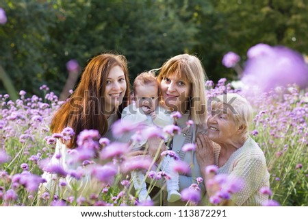 Four generations of beautiful women standing in a colorful lavender field - stock photo
