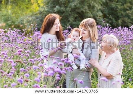 Four generations of beautiful women standing in a lavender field - stock photo