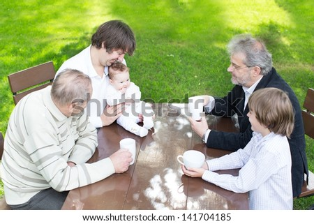 Four generations of men enjoying coffee in the garden - stock photo