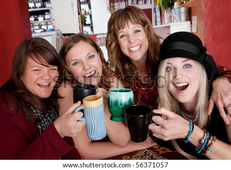 Four girlfriends enjoying time together at a bistro - stock photo