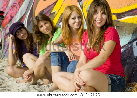 Four girlfriends near graffiti wall.