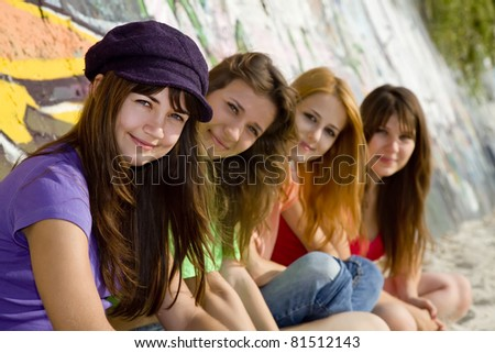 Four girlfriends near graffiti wall. - stock photo