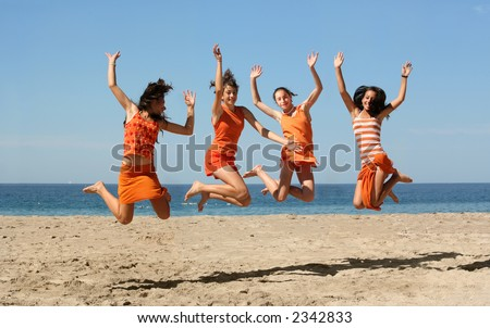 Four girls in orange clothes jumping on the beach - stock photo