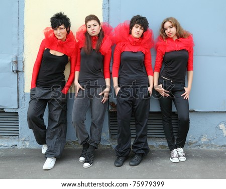 Four girls in same red-black clothes standing and leaning on the wall