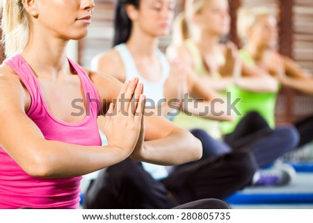 Four girls meditating after fitness training in gym - stock photo