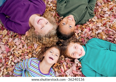 Four Girls Playing in Fall Leaves - stock photo