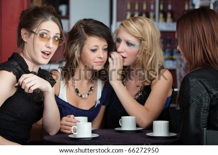 Four girls sharing secrets in a small cafe